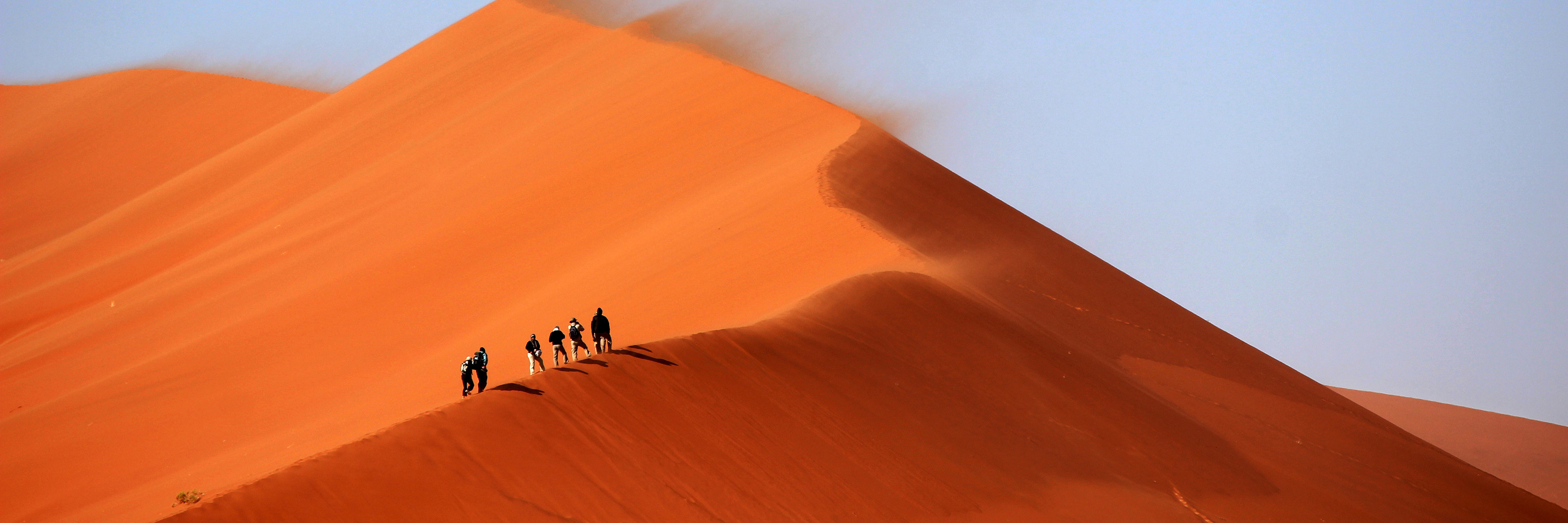 hiking a red sand dune - namibia destinations