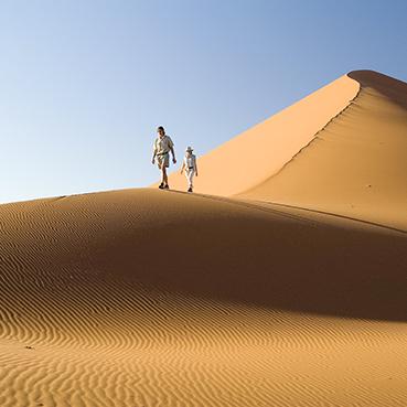 A couple walking the Namibian desert dunes